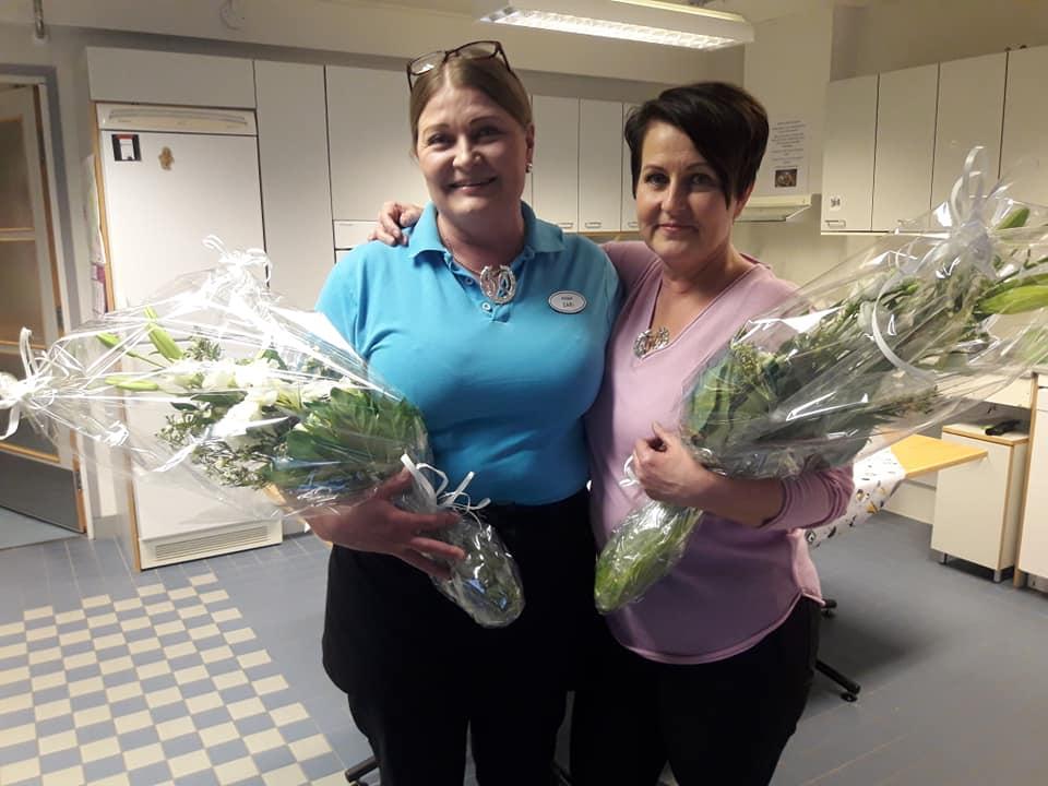 Kaksi työntekijää hymyilevät kameralle kukkakimppujen kanssa.
