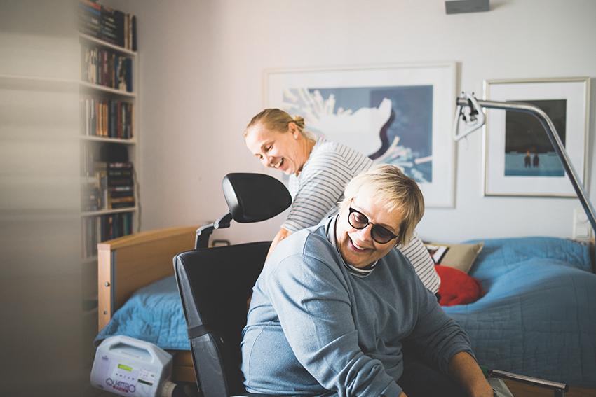 Hoitaja korjaa asukkaan istuma-asentoa tämän ollessa sähköpyörätuolissa.