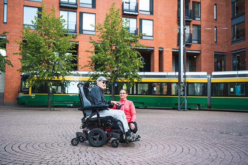 Henkilö istuu pyörätuolissa avustaja vierellään Merenpisaran edustalla. Merenpisaran edestä menee raitiovaunu.