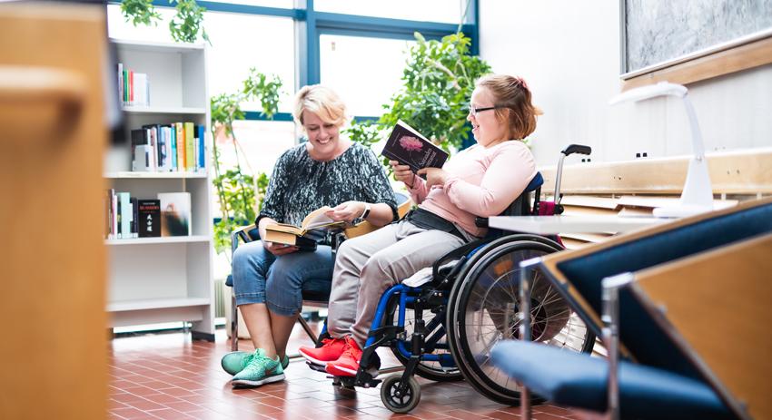 Kaksi naista istuvat kirjastossa ja lukevat kirjoja.
