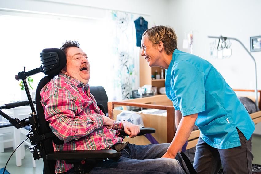 Asukas istuu sähköpyörätuolissa. Hoitaja on hänen edessään kumartuneena asukasta kohti ja hymyilee.