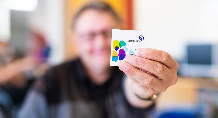 Asukas ojentaa kameraa kohti käden, jossa on neliön muotoinen paperi Neuroliiton logolla.