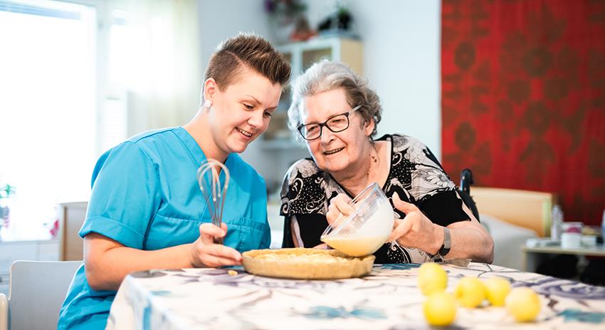 Hoitaja ja asukas leipovat yhdessä pöydän ääressä.